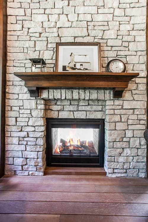 A closer look at the glass-enclosed fireplace fitted on the stone pillar and lined with a wooden mantel.
