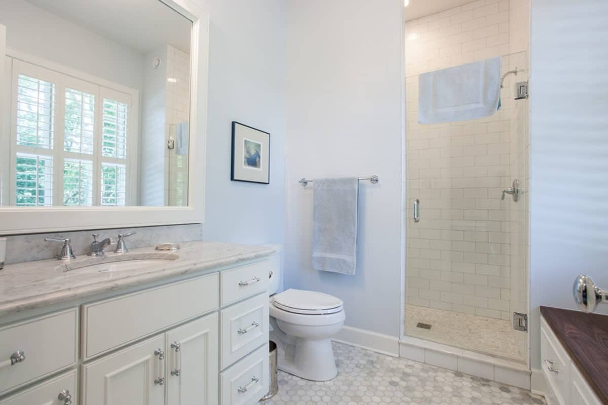 The bathroom offers a walk-in shower, a toilet and a marble top vanity under the white framed mirror.