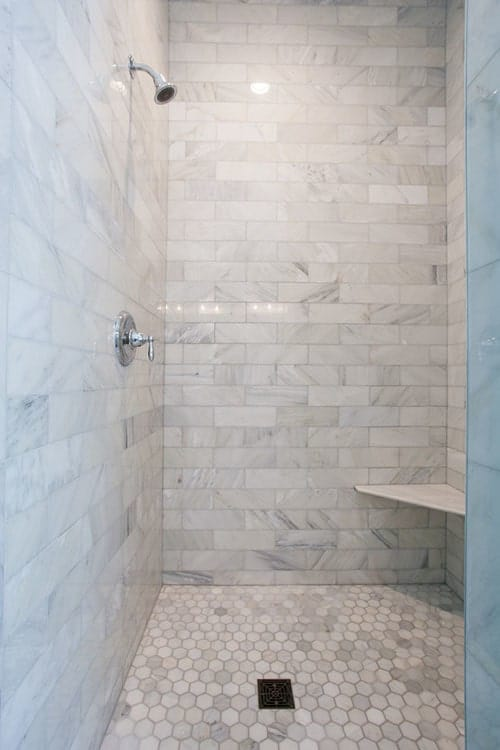 The walk-in shower has a hex tile flooring, corner tiled seat brick walls fitted with chrome fixtures.