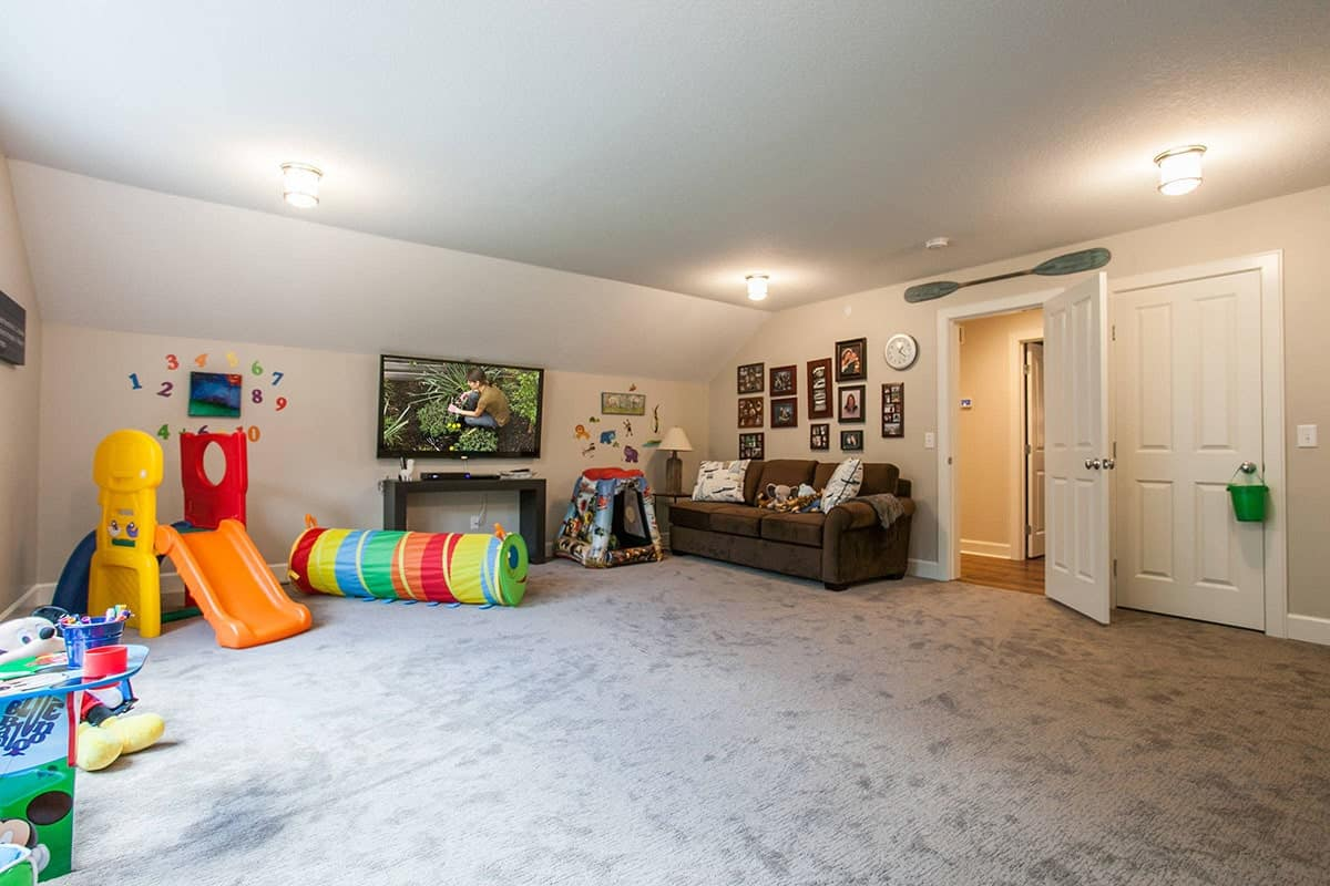 Media room and playroom loaded with toys, a brown sectional and a TV fixed above the console table.