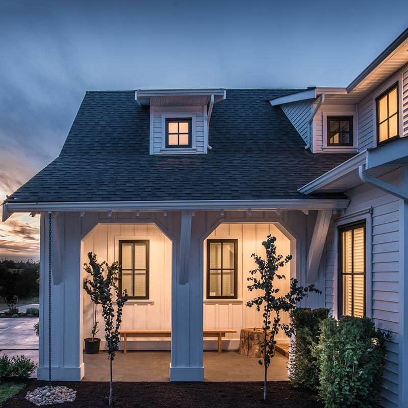 Side view of the front porch with a warm glow framed with white columns.