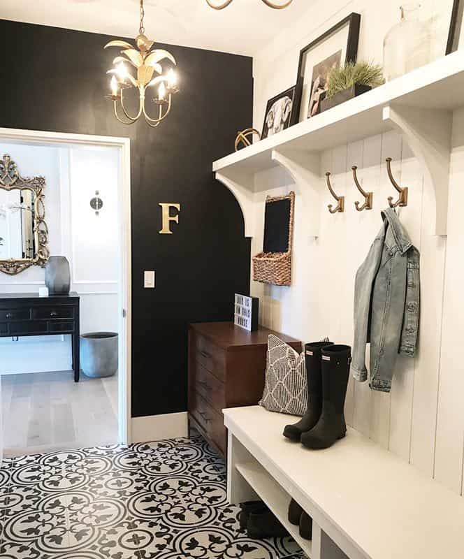 Right next to the mudroom is the powder room with dark wood vanity and a dazzling ornate mirror.