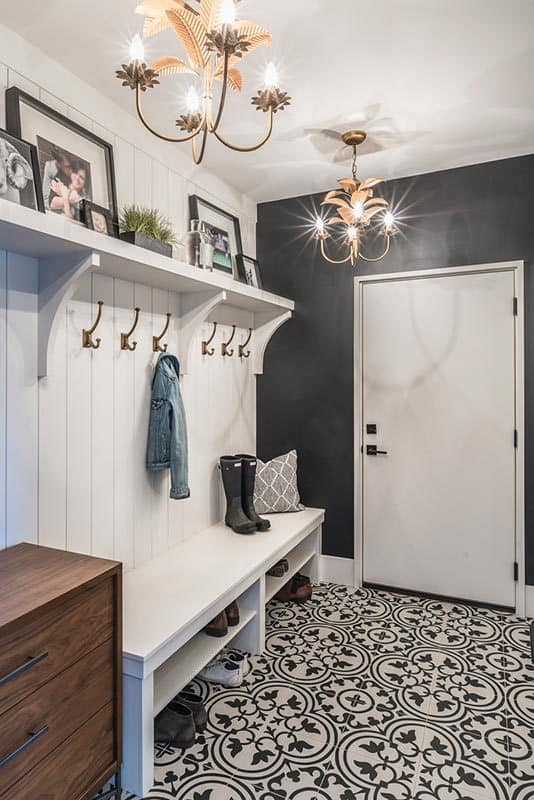 Mudroom with decorative tile flooring, lovely copper chandeliers and built-in storage fixed against the beadboard wall.