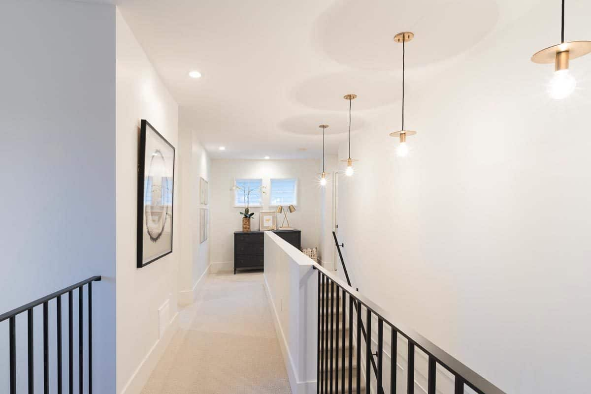Cozy ambient lighting flooded the second-floor hallway with white walls adorned by framed artworks.