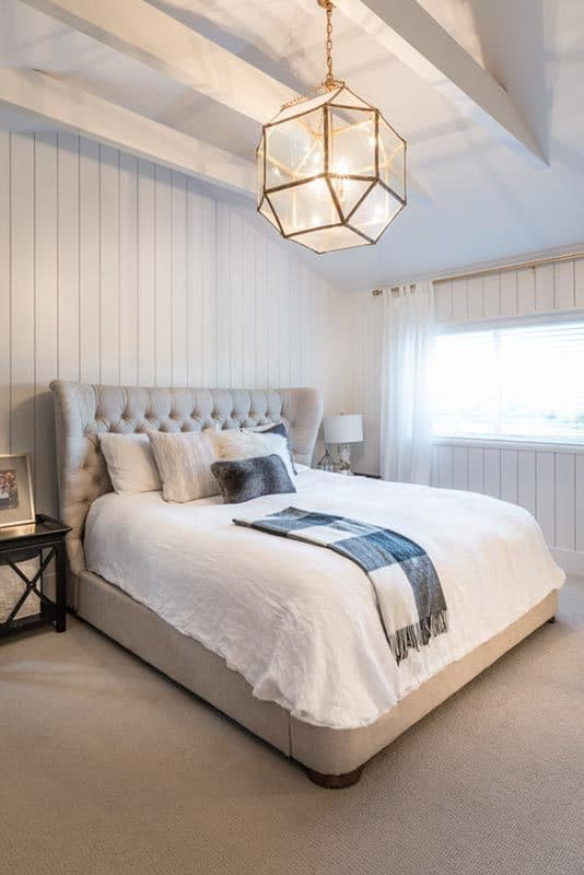 The bedroom includes white beadboard walls and a gray carpet flooring matching the tufted wingback bed.