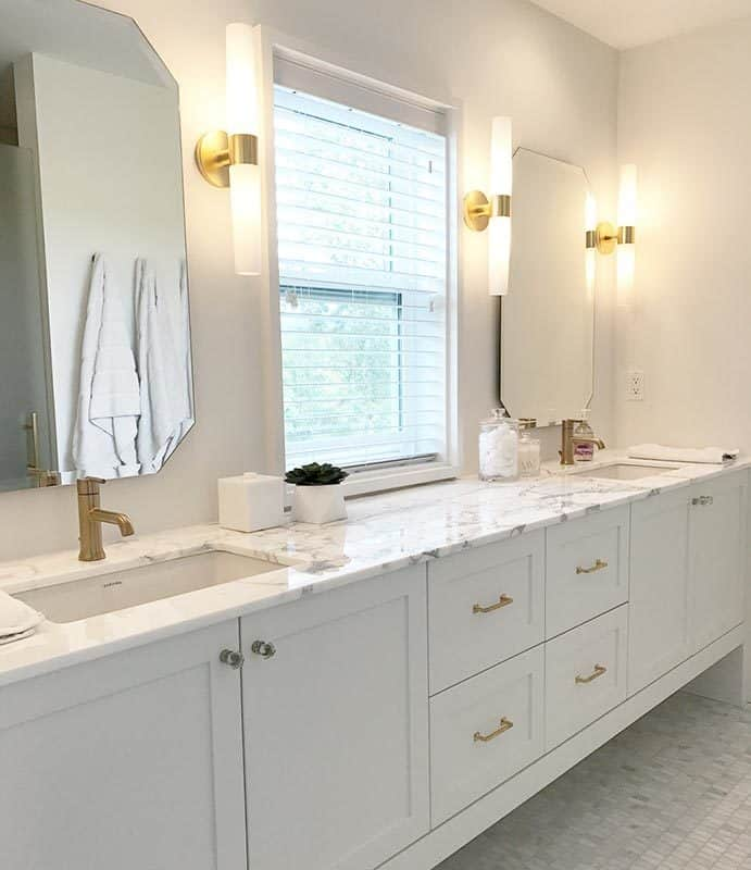 The bathroom is equipped with a dual sink vanity paired with octagonal mirrors and cylindrical sconces.