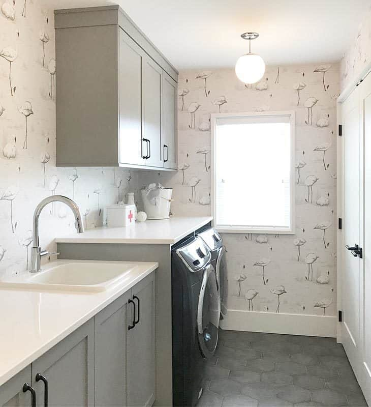 Laundry area with hex tile flooring and patterned wallpaper that adds character in the room.