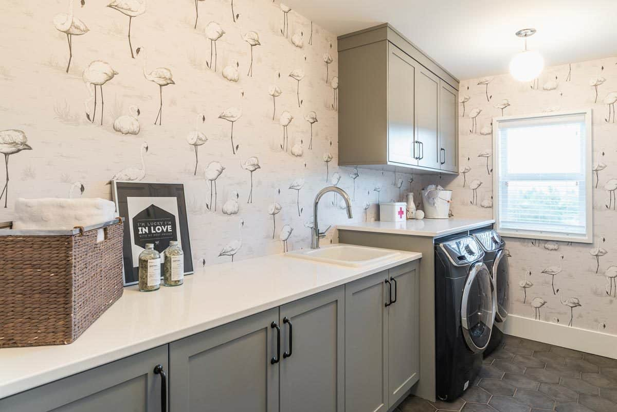 The laundry room offers a washing machine, a dryer, and gray modular cabinets.