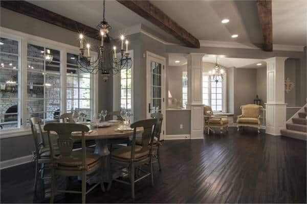 Breakfast nook with a round dining set and a candle chandelier hanging from the beamed ceiling.