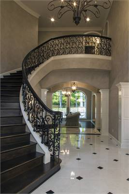 Foyer with an ornate chandelier and a curved staircase framed with intricate railings.