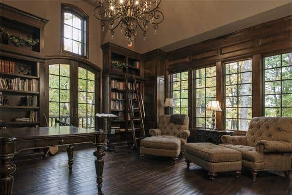 The home office is filled with dark wood desk, tufted seats, ornate chandelier, and built-in bookcases lined with a ladder.