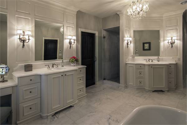 This view shows the sink vanities and a walk-in shower adjacent to the dark wood door.