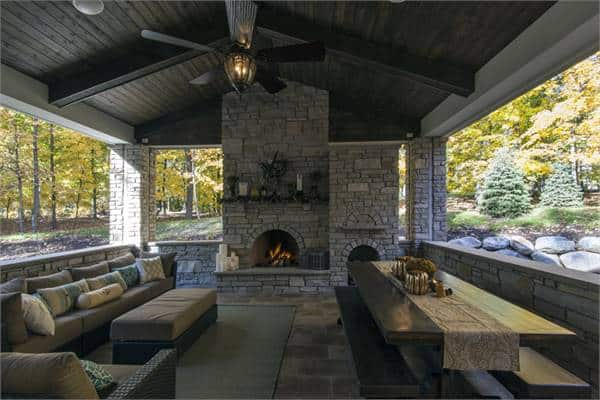 Covered porch with cushioned seats, wooden dining table, and stone fireplace under the beamed cathedral ceiling.