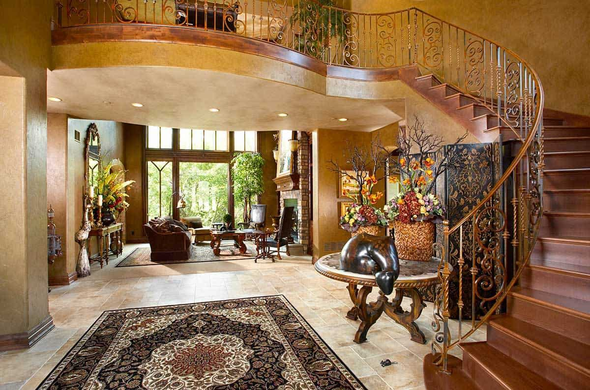 Foyer with an elaborate curved staircase and a view of the living room.