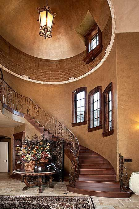 The turreted staircase is complemented with a large round table and illuminated by a lantern pendant light.