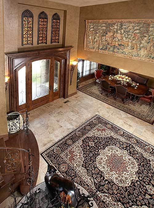 View of the foyer from the second-floor balcony showing the glazed front door and an immense classic rug that lays on the limestone flooring.