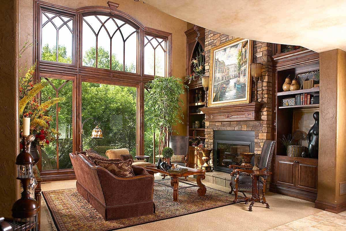 The living room has a stone fireplace, wooden built-ins, and massive glass windows bringing an abundance of natural light in.