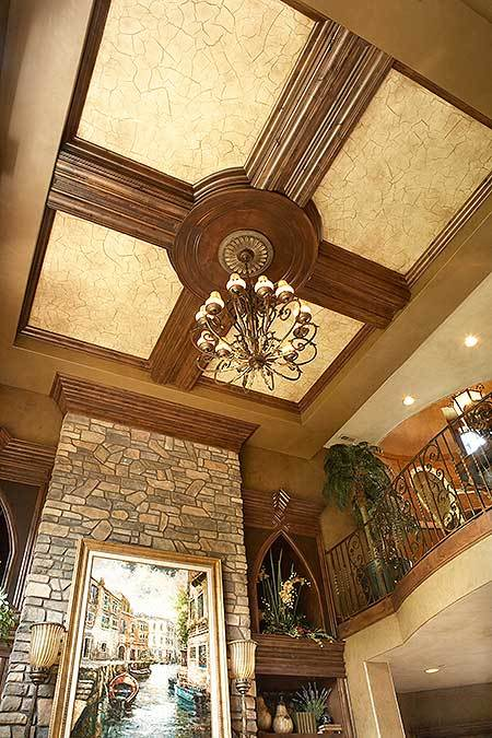Stylish tray ceiling of the living room mounted with an ornate chandelier.