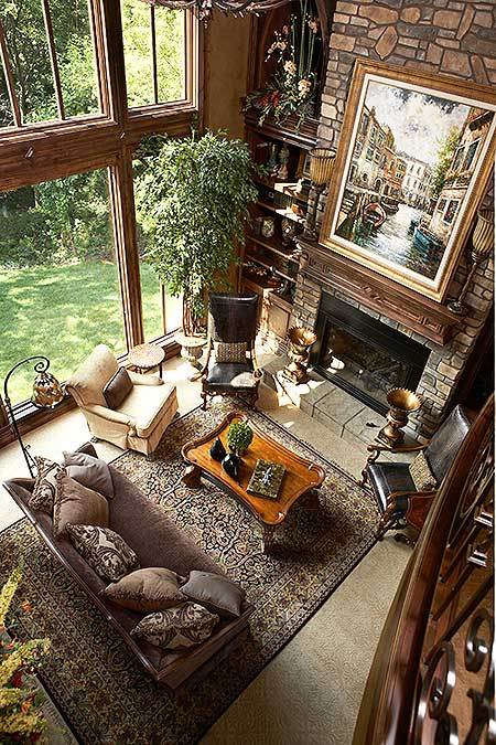 The top view of the living room shows the cozy seats and a wooden coffee table over the vintage area rug.