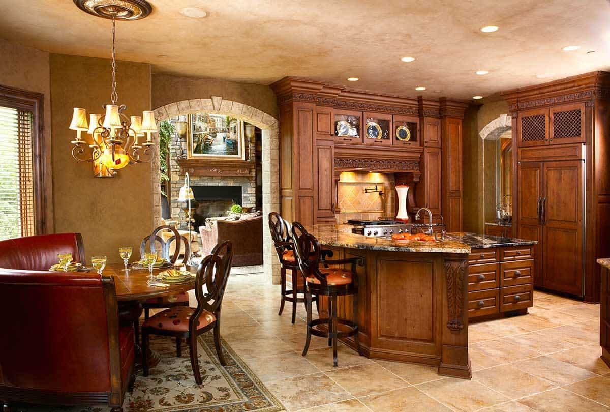 Kitchen with natural wood cabinetry, a center island, a curved peninsula, and a breakfast nook across.