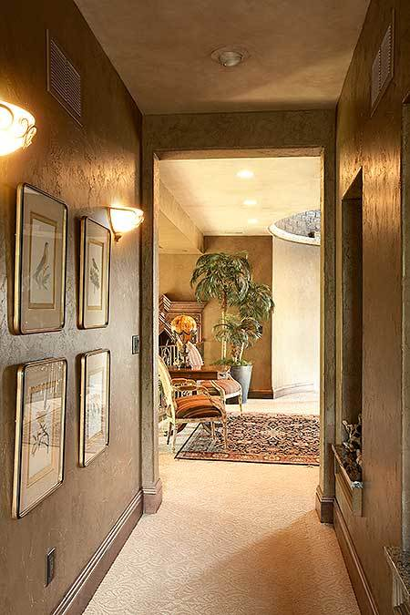 Hallway decorated with inset niche and framed artworks flanked by warm glass sconces.