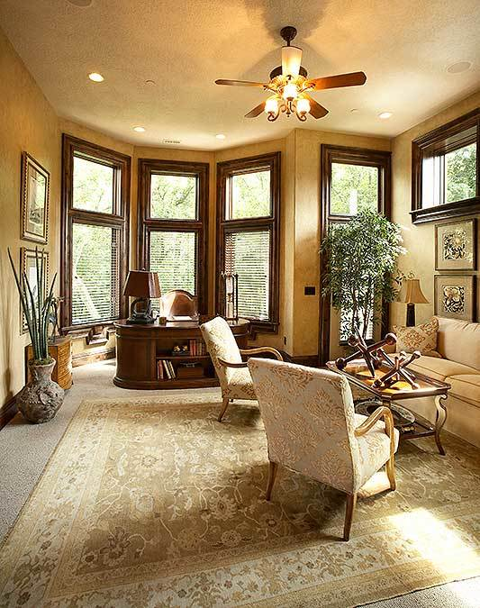 Home study with a sitting area and a bay window filled with an oval desk and a leather chair.