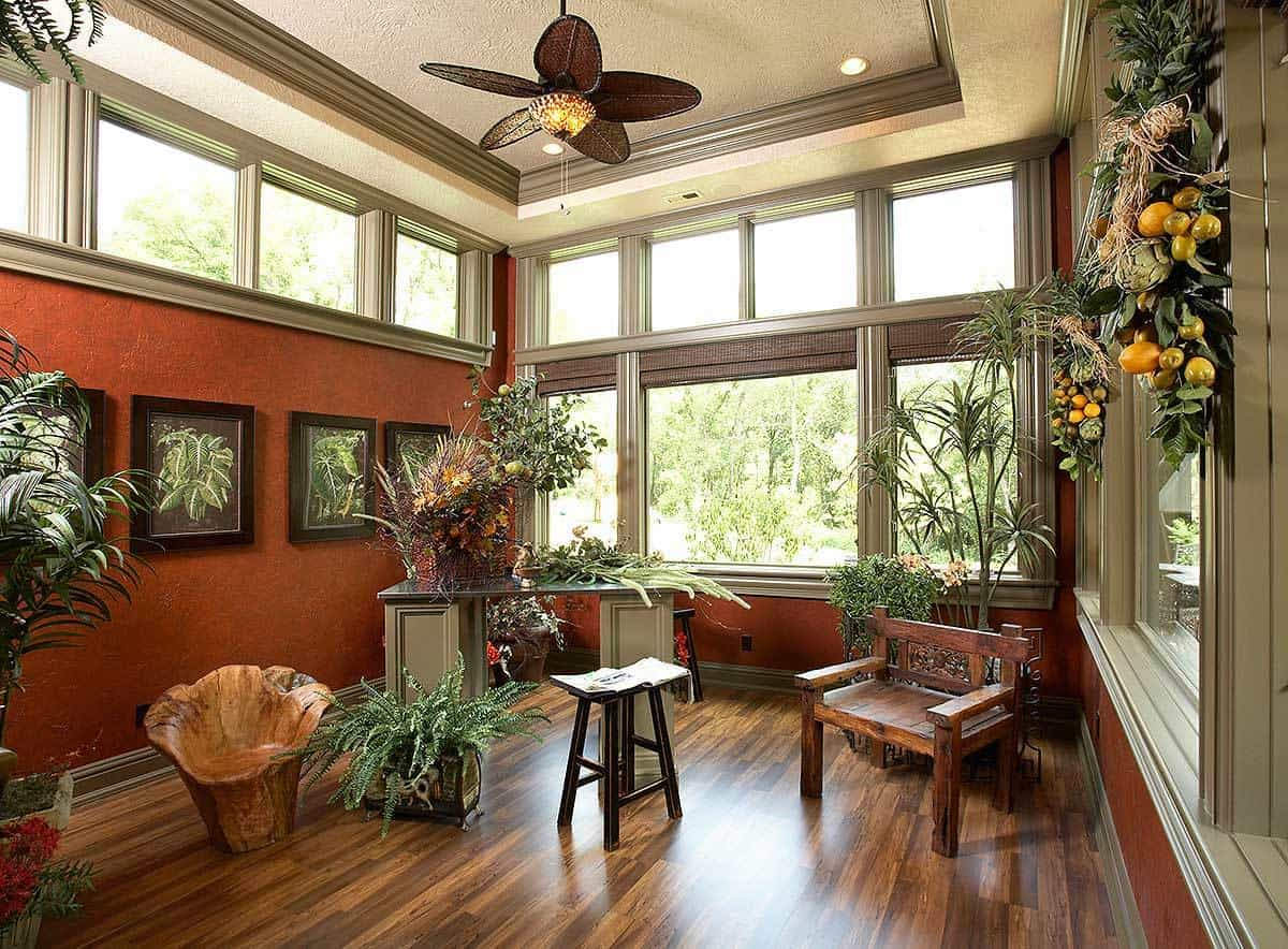 The craft room is filled with wooden furniture, fresh green plants, foliage artworks, and a fan mounted on the tray ceiling.