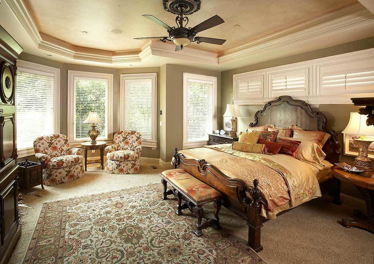 Primary bedroom with a tray ceiling, green walls, and a sitting area by the bay window.