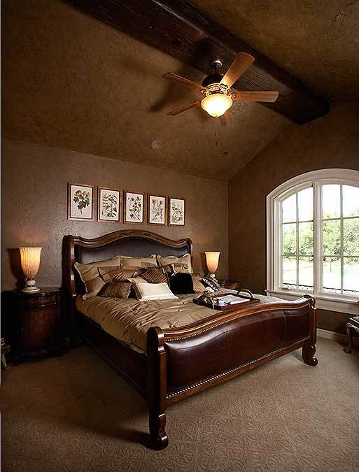 This bedroom has textured carpet flooring and dark walls matching with the vaulted ceiling that's lined with a rustic beam.