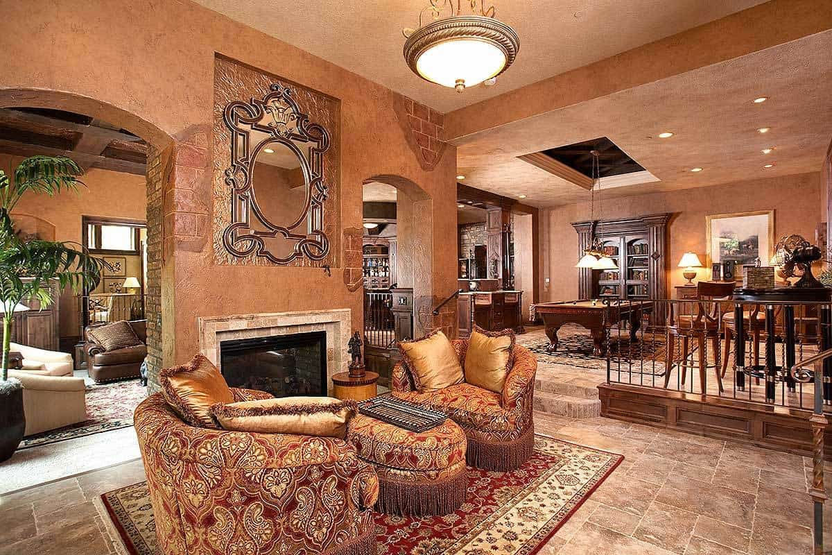 The recreation room offers classy seats, a matching ottoman, and a glass-enclosed fireplace with a stylish mirror on top.