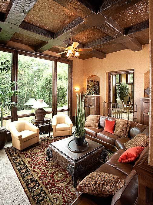 Family room with wooden coffered ceiling, full-height windows, and cozy seats paired with a carved coffee table.