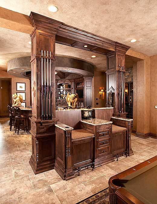 Built-in pool chairs in the game room attached to the granite top bar lined with wooden columns that double as stick racks.