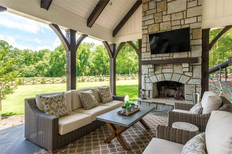 Covered porch with a stone fireplace and wicker cushioned seats paired with a wooden coffee table.