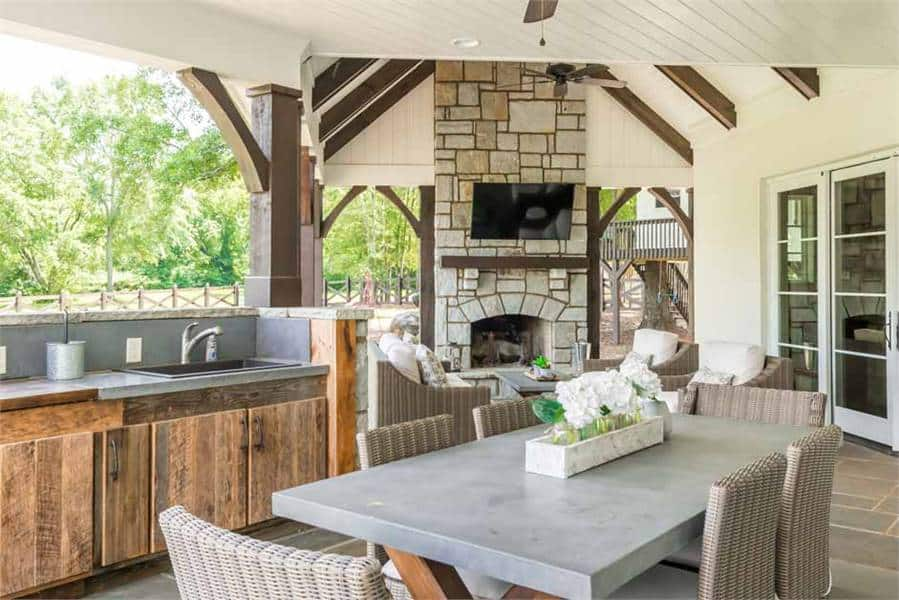 The outdoor kitchen offers rustic wooden cabinets and an undermount sink along with a wicker dining set.