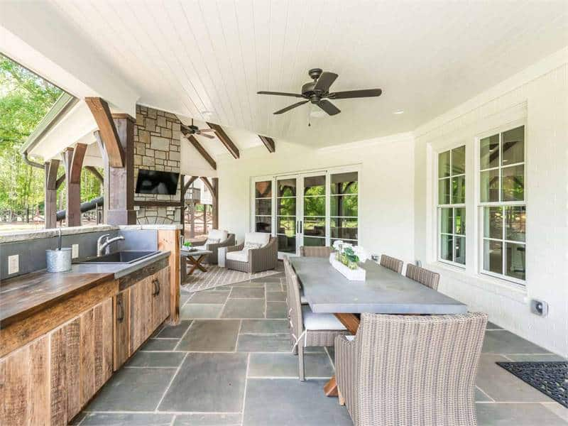 The open layout view of the covered porch shows the outdoor kitchen, dining and living area.