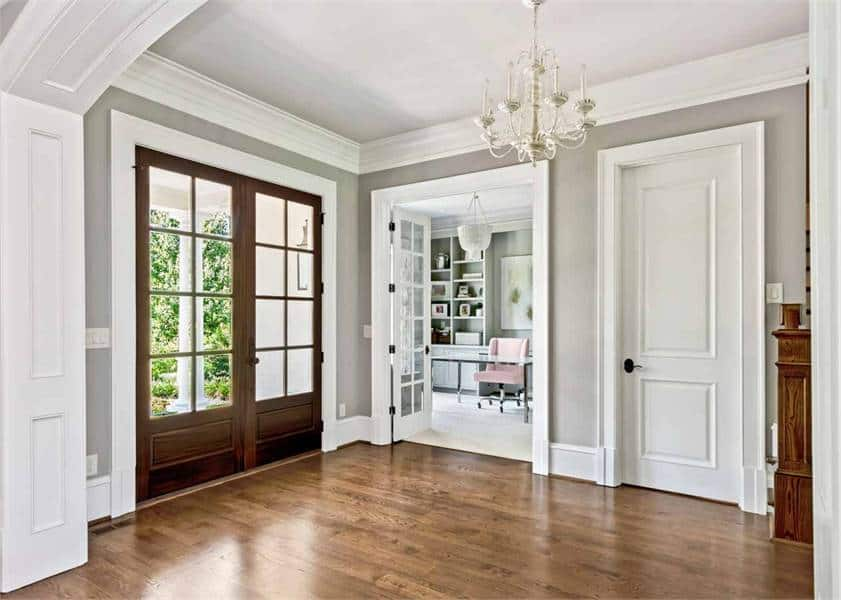 Foyer with a wooden french front door, a candle chandelier, and natural hardwood flooring.