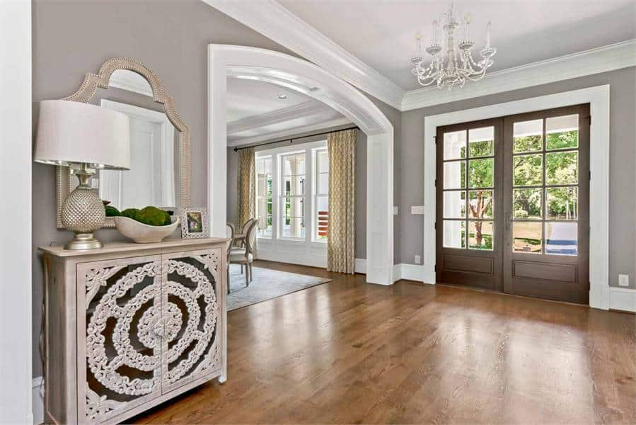 The foyer is furnished with an ornate console table complemented by an arched mirror and drum table lamp.