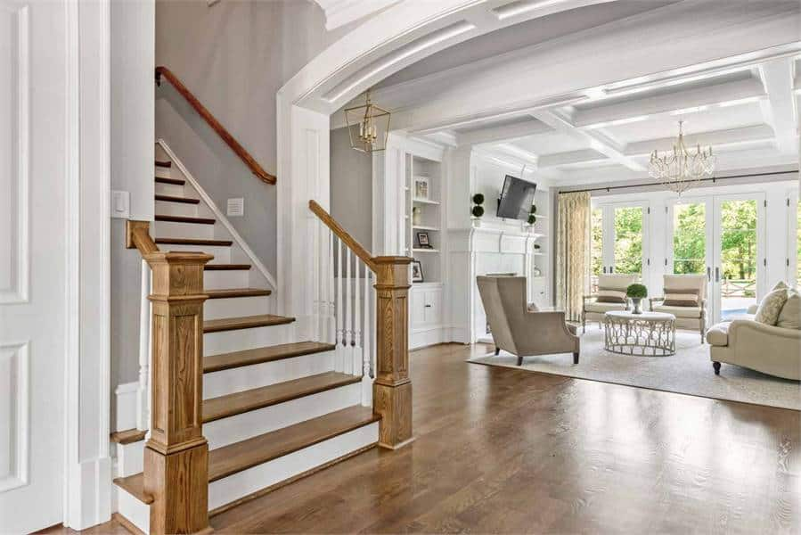 A traditional staircase in front of the living room that leads to the bedrooms.