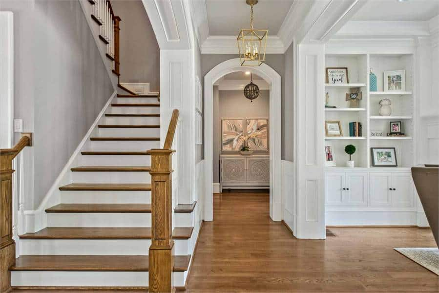 Traditional staircase and built-in shelves flanked the niche that's framed with an archway lit by the brass caged pendant.