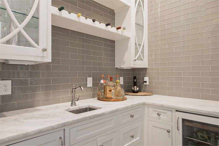 Pantry with white cabinets, marble countertop, and a wine shelf sandwiched by glass-front cabinets.