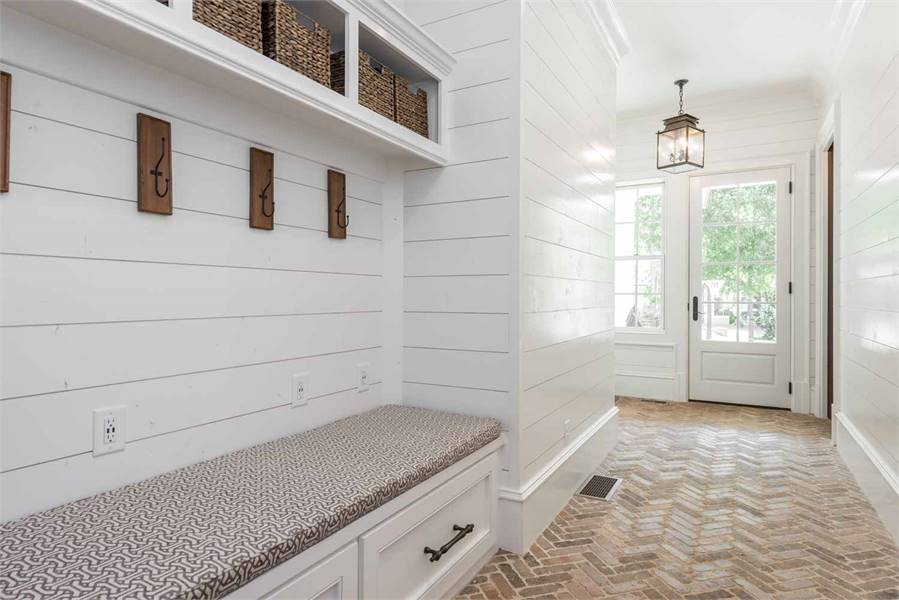 Mudroom with built-in storage and a parquet flooring arranged in a herringbone pattern.