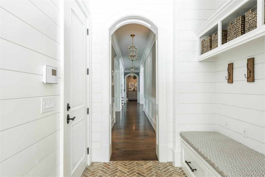 Opposite view of the mudroom shows the hallway with rich hardwood flooring and open archways.