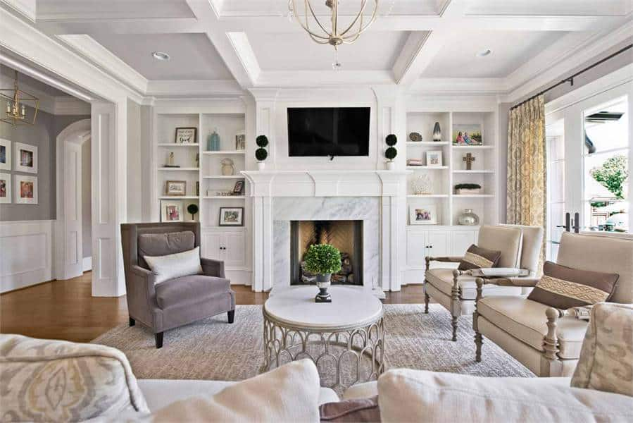 The living room features a marble fireplace with a TV on top and built-in shelves on the sides.