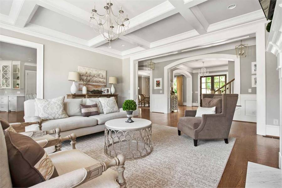 The living room is furnished with cushioned seats and a gorgeous round coffee table over a beige textured rug.