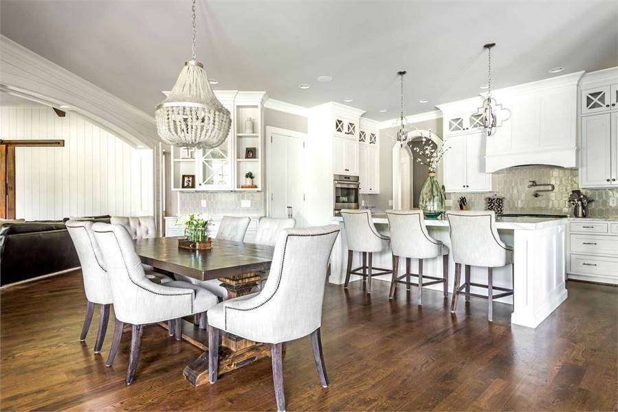 Behind the living room is the dine-in kitchen with natural hardwood flooring and a regular gray ceiling mounted with recessed lights and dazzling pendants.