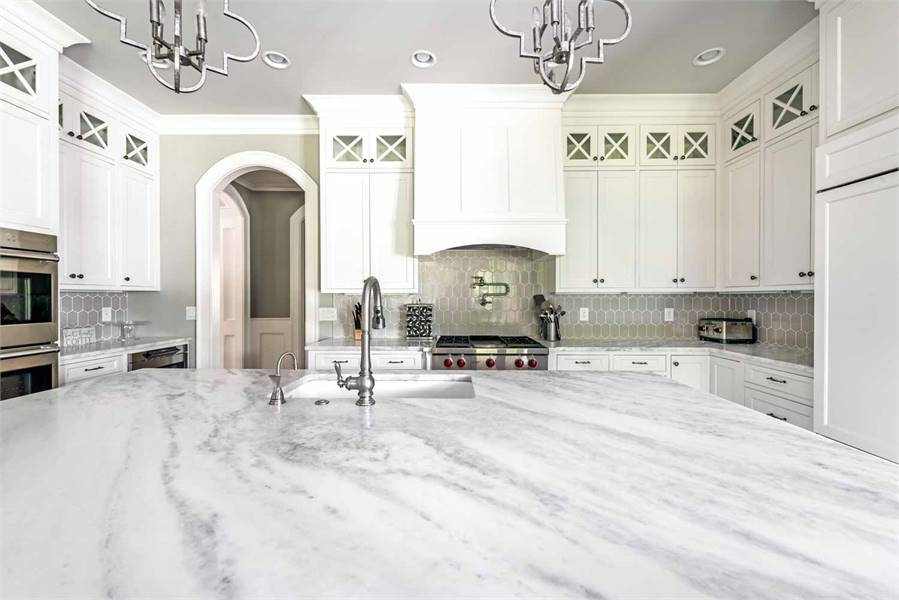 A closer look at the kitchen shows the marble countertops and white cabinetry fixed against the gray tiled backsplash.