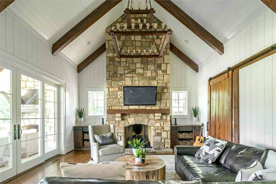 Keeping room with shiplap walls and a cathedral ceiling lined with dark wood beams.