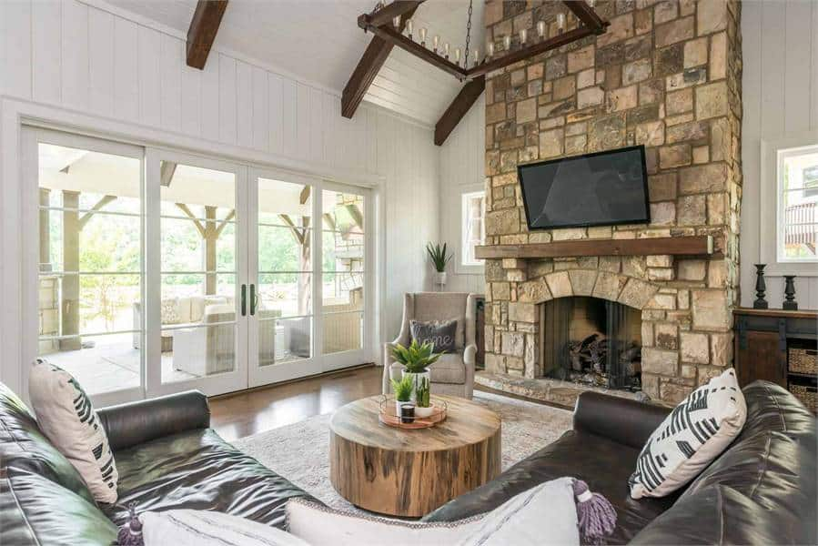 Angled side view of the keeping room shows the stone fireplace and a french door that opens out to the lanai for extended entertainment.