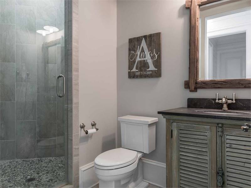 Bathroom with walk-in shower, a toilet, and sink vanity with louvered cabinets and a rustic mirror.