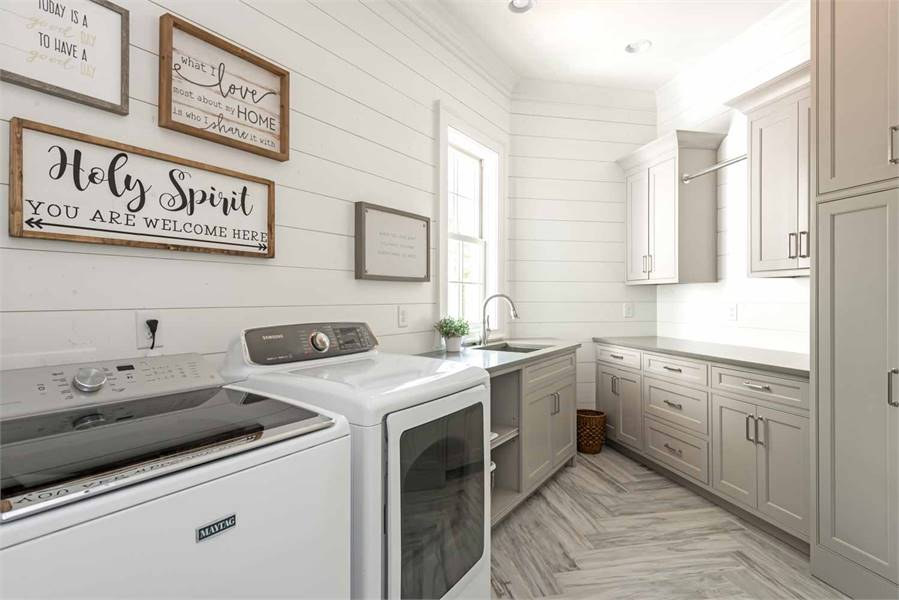 Laundry room with herringbone tiled flooring and white shiplap walls adorned by framed artworks.